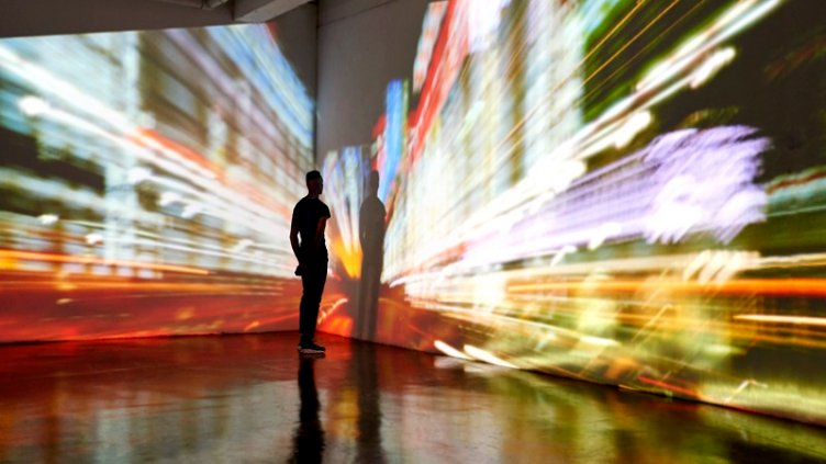 Man looking at abstract city scape being projected in a gallery space